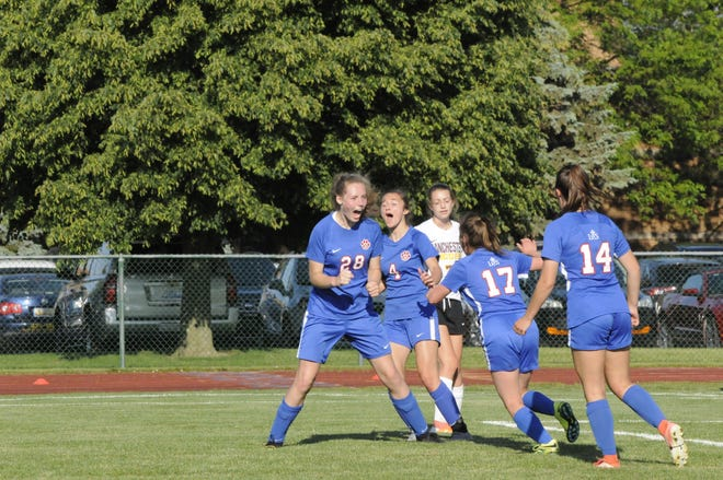 Lenawee Christian's Lauren Swiggum celebrates a goal in the district final against Manchester while Janae Good (4), Sydney Knoll (17) and Natalie Morr (14) race to celebrate.