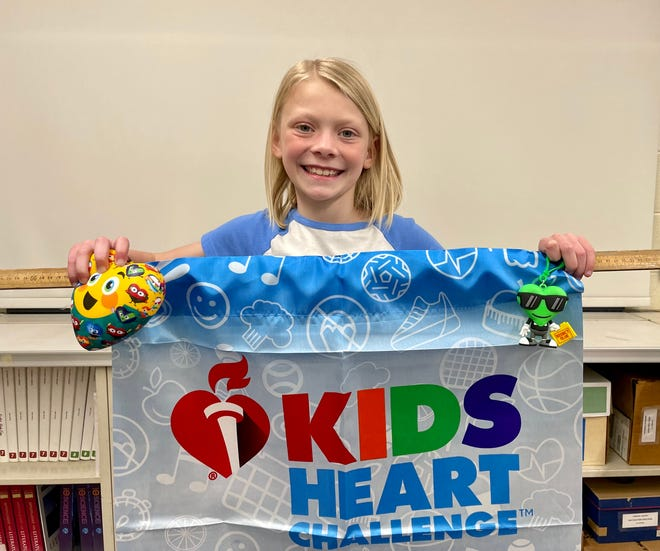 St. Stephen Lutheran School third grader Allie Switney holds up a banner and American Heart Association character Agent KHC, during the Adrian school's monthlong project to promote healthy lifestyles. Switney was one of two students that raised more than $1,000 in donations to benefit the Heart Association.
