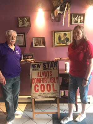 David and Lois Furioso hold the old poster at Dansville's Star Theatre, which is marking its 100th anniversary.