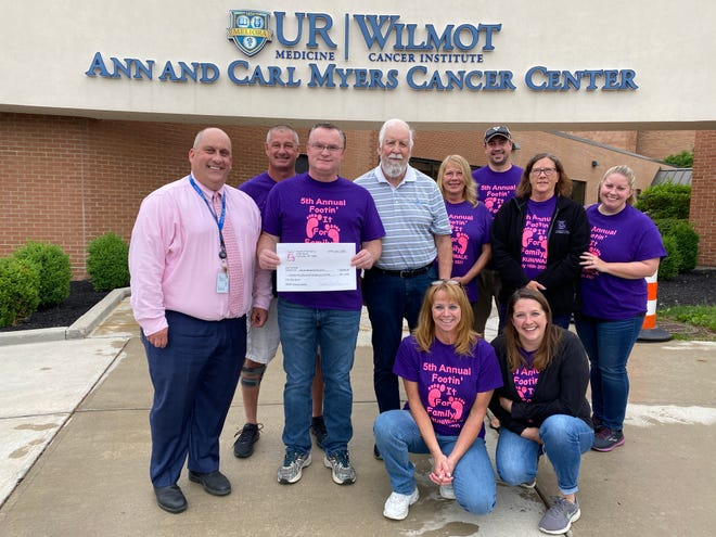Footin' it for Family committee members drop off a check for $25,000 for the Ann and Carl Myers Cancer Center at Noyes Memorial Hospital.