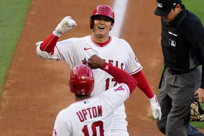 Los Angeles Angels designated hitter Shohei Ohtani (17) celebrates with Justin Upton (10) after they both scored off of a home run hit by Ohtani during the first inning of Tuesday's game against the Kansas City Royals in Anaheim, Calif. The 470-foot blast was the longest home run of Ohtani's career as the Angels hit five homers in an 8-1 rout of the Royals.