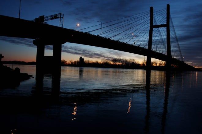 The sun rise silhouettes the Great River Bridge over the Mississippi River in Burlington.