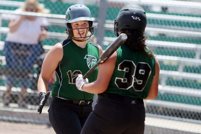 West Burlington-Notre Dame's Abbey Bence (12) is congratulated by teammate Lyndsey Kelley (39) after scoring a run during their game against Hillcrest Academy Wednesday June 9, 2021 at West Burlington's Barb Carter Field.