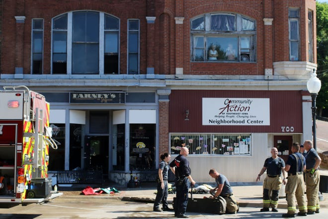 Members of the Burlington Fire Department clean up after responding to a fire Wednesday at Farney's on Jefferson Street in downtown Burlington. Customers noticed smoke and flames coming from the front door leading upstairs above the bar. The fire was quickly extinguished, no damage was reported inside the bar and owner Rich Adams expected to reopen a short time later.