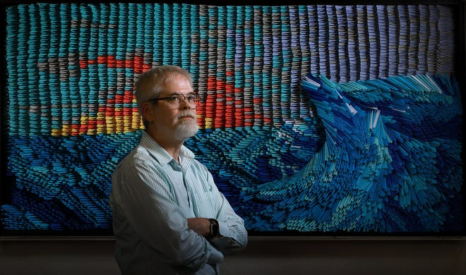"""Artist Clifford Buckley, a member of Congregation Ahavath Chesed, created """"Ebb and Flow,"""" an origami creation designed to represent life during the COVID-19 pandemic. It's made up of more than 5,000 folded paper triangles, some 275 of which have messages written or drawn by the congregation's members."""