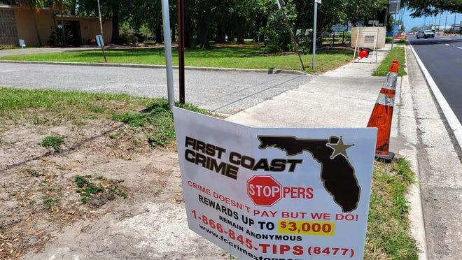 A First Coast Crime Stoppers sign marks the site in front of Woodstock Park where a teenage boy shot and killed June 8.