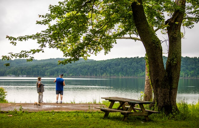 Linda Schloesser, left, and Paul McGlocklin, right, enjoy their morning coffee Wednesday with their dog Buddy while looking over Lake Monroe at the Cutright State Recreation Area.