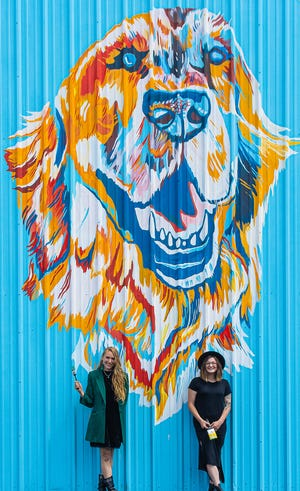 Sabrina Osment and Daily Ralston in front of one of their murals at Sunny's Marina.