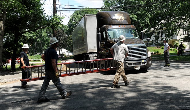 Utility workers approach a UPS tractor trailer on Willowbrook Drive in Framingham, June 9, 2021. A utility pole was pulled down across the road behind the truck. Traffic was shut down.