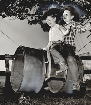 In June 1961, Jana Lee and Marvin Paul Shoulders ride a bucking barrel their father, rodeo legend Jim Shoulders, had strung on a steel cable between two trees on the family ranch in Henryetta.