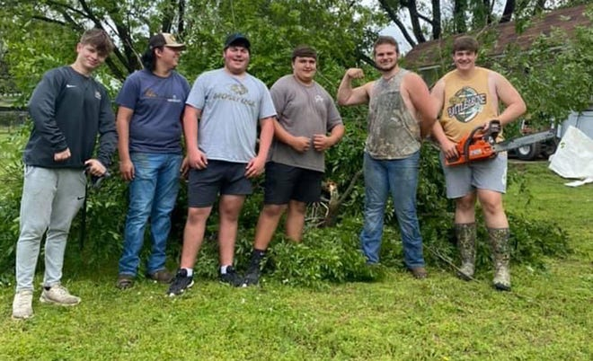 Brilee White (from left), Anthony Garcia, Logan Johnson, Zane Hulburt, Ethan Thrift, and Nathan Smith take a small break after helping the Alma community remove trees and limbs that fell after a storm swept through the community back in May.
