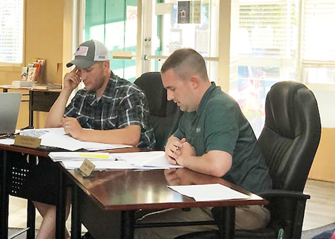 Treasurer Bryan Rowold reviews information before the Chenoa City Council Tuesday night while Commissioner Joseph Bell, left, listens.