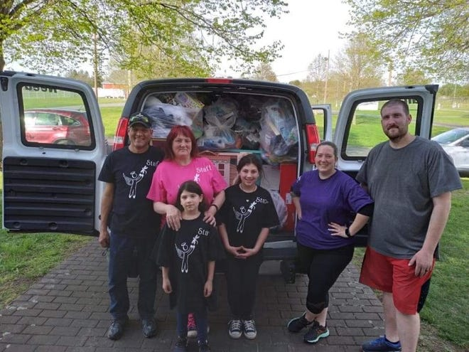 Sherry Scott (in pink) poses with volunteers in front of a van full of donations for Angels & Dragonflies. The non-profit is hosting a food truck festival fundraiser this weekend at Mountain View Vineyards.