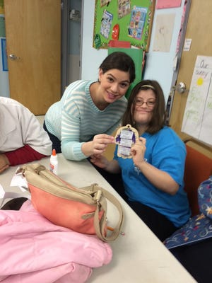 Stephanie Quinto helps a student at the Yad Hebrew School show off a project.