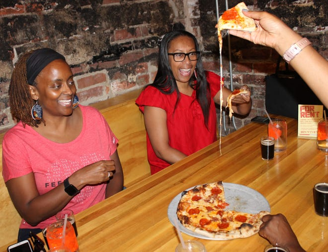 Friends enjoy craft beer and pizza at Trapezium Brewing Company in Petersburg, Va. in Sept. of 2019.