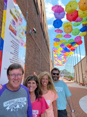 Umbrella Alley in downtown Louisville has become a focal point of events, music and art. Overseeing the alley are from left: Rick Guiley, Raeann Guiley, Tonda Mathie and David Yeagley. The colorful attraction draws visitors from both near and far. A July Fourth weekend celebration is also planned there for the second consecutive year.