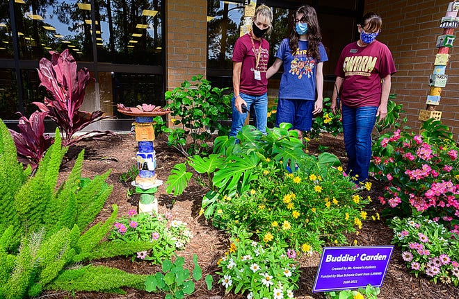 Amy Arnow, a teacher for students with intellectual disabilities and autism at St. Augustine High School, stands with student Erica Walker and paraprofessional teacher Kim Elswick in a flower garden her students planted and tend to next to the school's library on Wednesday.