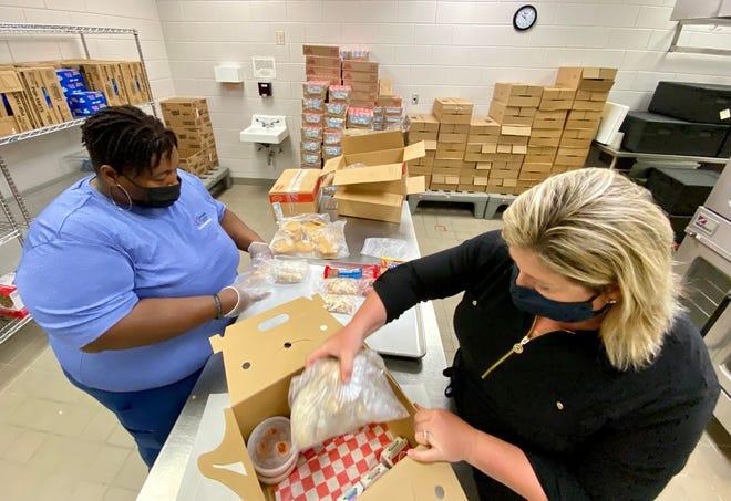 Brooke Watkins and Jada Brown unpack a meal kit at Kings Mountain Intermediate School.