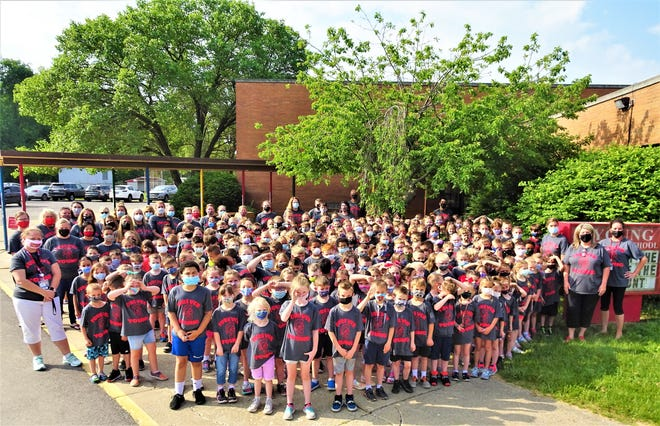 Students and staff at Young Elementary School in Springfield Township gather for a group picture outside the building on the last day of school on May 26.