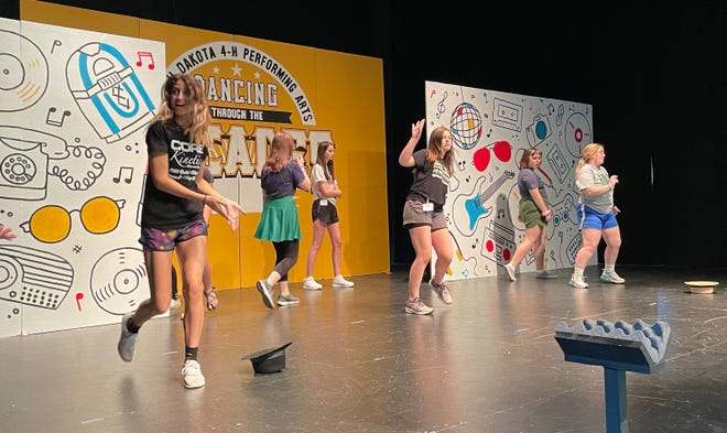 South Dakota 4-H Performing Arts troupe members, from left, Breanna Roth, Jerica Ratigan and Paige Peterson practice their danceoff routine on stage at the Northern State University Krikac Auditorium Wednesday. The 16-member group has been learning its show this week and will have performances Friday at 7 p.m. and Saturday at 10 a.m. This year's show is Dancing through the Decades. The troupe will perform later this summer at Spink County Achievement Days, the Brown County Fair and the state fair.