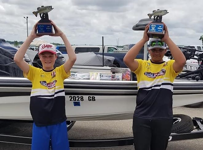 From left, the Topeka Jr. Hawgs team of Laiken Emanuel and Avery Bowen hold up their Kansas BASS Nation Junior State Championship trophies after winning the title June 5-6 at Milford Reservoir.