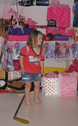 Dylan Wetzel, 6, poses next to some of the gifts included in the Wednesday unveiling of an indoor hockey rink in the basement of her Keedysville home.  The skating rink, revealed on Wednesday, was made possible by Make-A-Wish Mid-Atlantic.