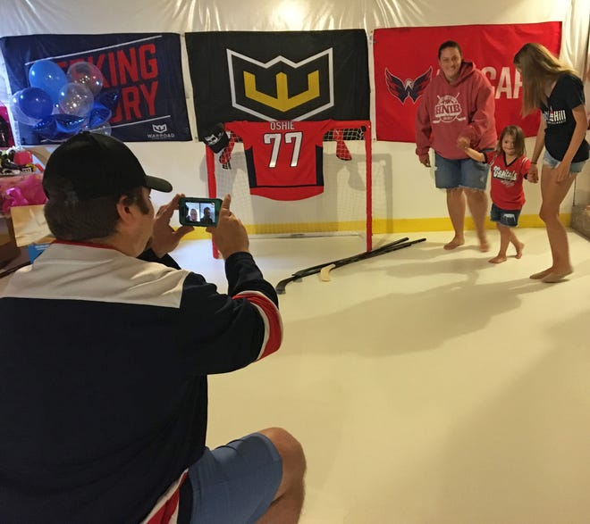 Chris Wetzel captures the moment Wednesday when his daughter Dylan Wetzel, 6, gets her first glimpse of the indoor hockey rink in the basement of their Keedysville home made possible thanks to Make-A-Wish Mid-Atlantic.  Mum Mandy Wetzel and sister Devin Glens, 14, help Dylan through slippery artificial ice.
