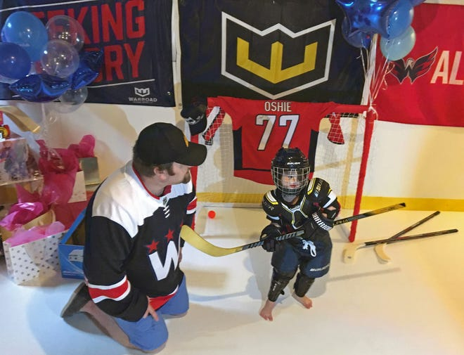 Chris Wetzel smiles as his daughter Dylan Wetzel, 6, tries her new hockey gear Wednesday on the indoor rink in the basement of their Keedysville home.
