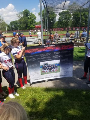 The BNL girls softball players present this District 5 Coach of the Year banner to head coach Brad Gilbert following the semistate game Saturday.