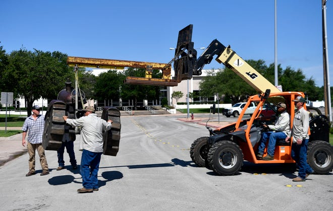A city crew carries the Otis the Tractor sculpture to its place in the Adamson-Spalding Storybook Garden as local sculptor Steve Neves, left, looks on.