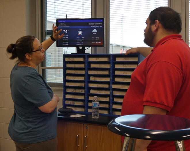 Dustin Tesso, Wynford's district technician, right, helps science teacher Julie Rexroad trouble-shoot a minor display issue with the district's WeatherBug system on Tuesday morning.