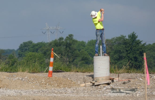 A worker pulls a wire through a concrete pillar as work continues north of the remaining portion of Wynford's old high school building. The area will become a parking lot.