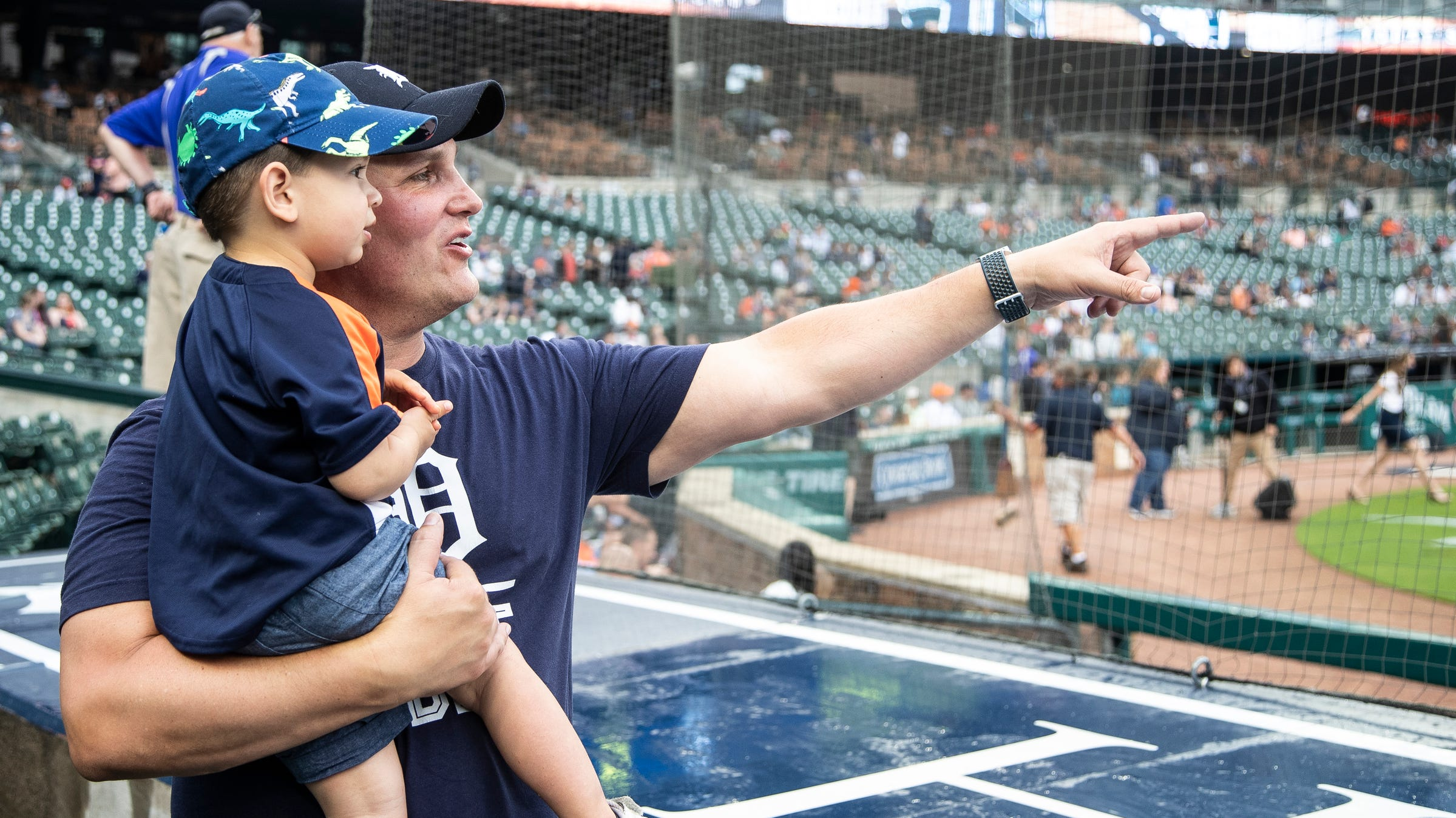 Laurence Buckley and his son Cameron, 2, watch Detroit Tigers players warm up before the game against Seattle Mariners at Comerica Park in Detroit, Tuesday, June 8, 2021.