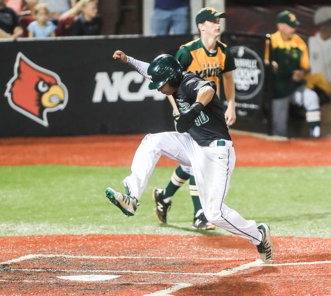 Trinity's Daylen Lile stomps on home plate to score the go-ahead run after an RBI by Korbyn Dickerson's single to right field as the Rocks defeated St. X 3-2 in the Seventh Regional Final Tuesday night. Lile was intentionally walked every time at bat. June 8, 2021
