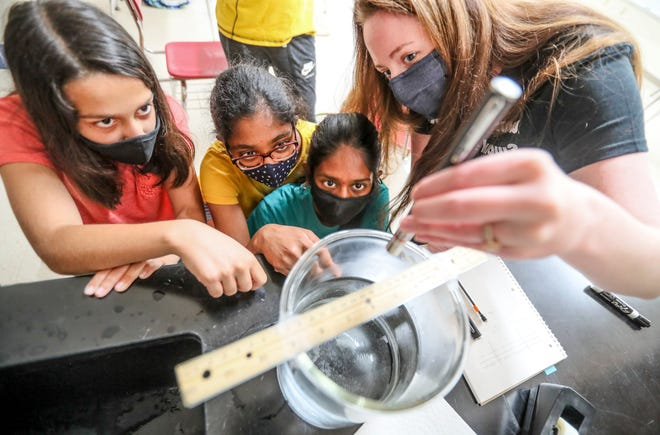 From left to right, Raghvi Sethi, 13, Radhika Gupta, 12, and Rishika Kommuri, 13, watch as Mallory Conlon, UW-Madison Department of Physics Quantum Science Outreach Program coordinator, shines a laser to see if different colored laser lights impact the light refraction in water. The students were participating in the Wisconsin Heights Summer Science Camp outside Madison.