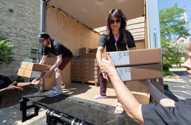 Digital Bridge employees Ayla Jensen, right, and Cody Welch unload donated laptops Wednesday at the United Way Of Greater Milwaukee & Waukesha County, 225 W.Vine St., in Milwaukee.
