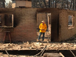 Arizona House Speaker Rusty Bowers walks through the remains of his family's weekend home on June 8, 2021. The home, near Globe and Miami, was destroyed by the Telegraph Fire the day before. Bowers used the home in the remote mountains as a family retreat and often did his artwork there.