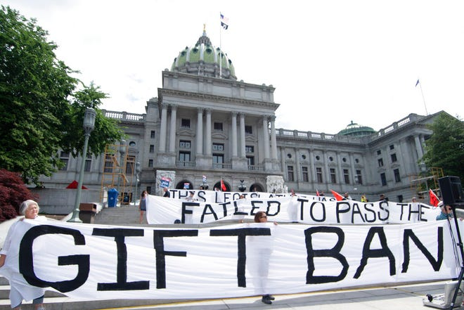 Demonstrators from MarchOnHarrisburg stand outside Pennsylvania's Capitol to press lawmakers to pass legislation banning them from taking gifts from lobbyists and others aiming to influence them, Wednesday, June 9, 2021, in Harrisburg, Pa. The Pennsylvania Legislature does not limit how much lawmakers can accept from lobbyists and others seeking to influence them. (AP Photo/Marc Levy)