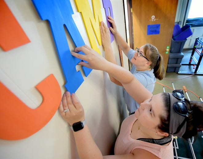 Camp Pennwood Camp Director Lindy Eisenhart, foreground, and Alicia Zienkiewicz, The Arc of York County director of community services, erect a sign at the clubhouse while preparing for summer campers Wednesday, June 9, 2021. The Arc of York County's Camp Pennwood will offer day camps running from July 5 through Aug. 6 this year. Bill Kalina photo