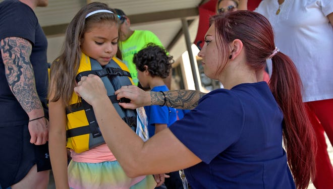 Mya Vasquez, left, gets fitted for a life vest by Destiny Simmons, right, during a Safe Kids San Angelo event promoting safe practices for young people at the Shannon Medical Center South location Tuesday, June 8, 2021.