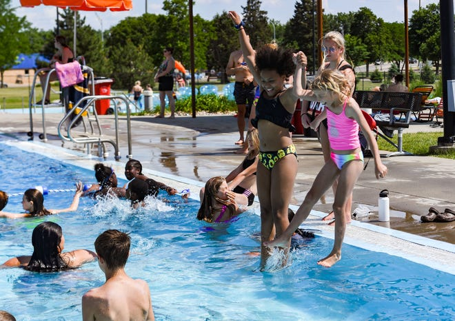 Ruthie Kent, 10, and Hope Christians, 8, hold hands while jumping into the pool on Wednesday, June 9, 2021, at the Drake Springs Family Aquatic Center in Sioux Falls.
