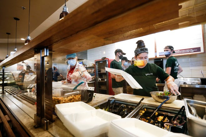 Neighbor's Mill Bakery & Cafe employee Maddy Upchurch prepares salads at the Independence Street location during lunch on Tuesday, June 8, 2021