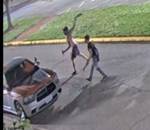 Two male suspects are pictured near a car that was damaged at Zane State College on June 8.