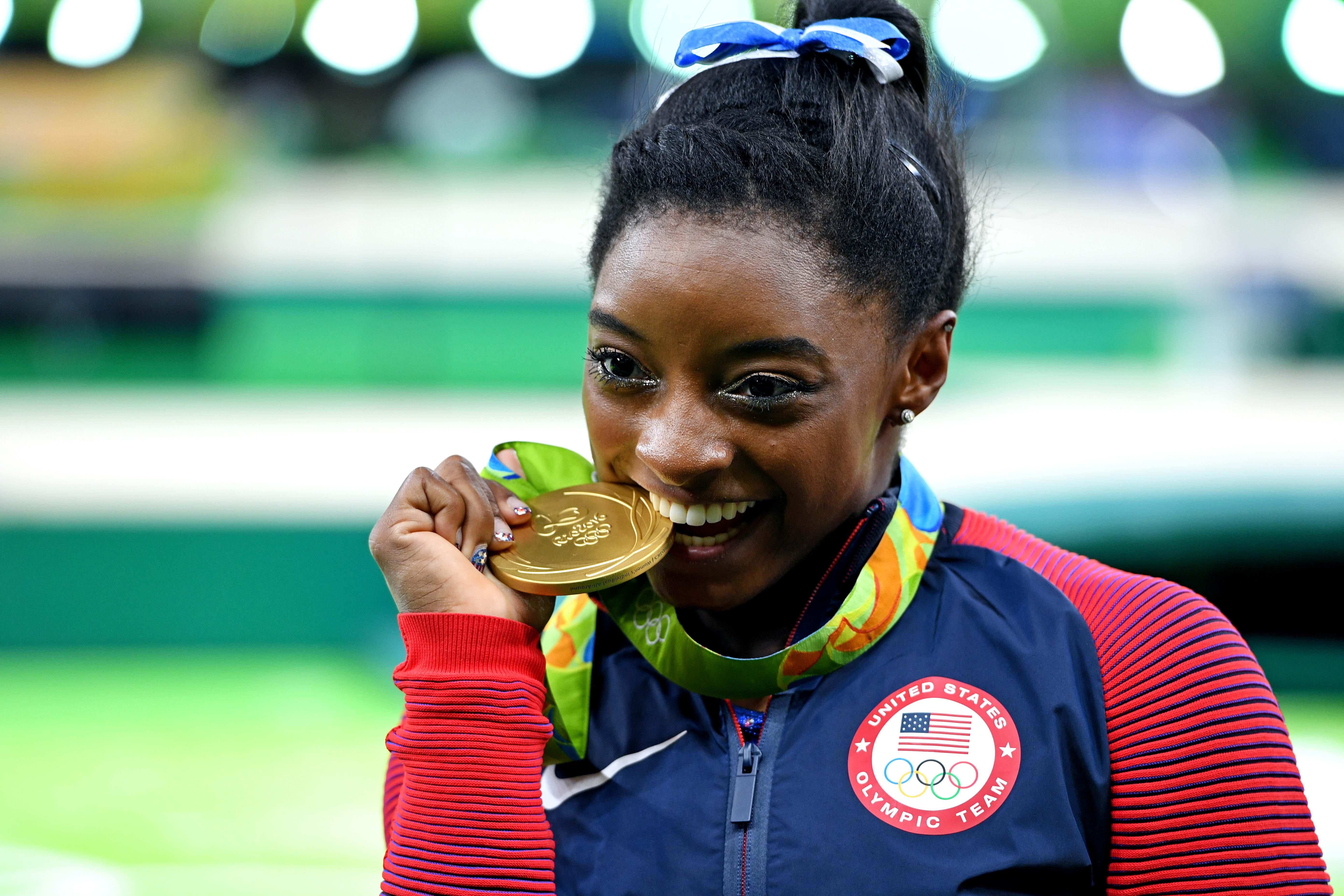 Simone Biles bites an Olympic gold medal in celebration.