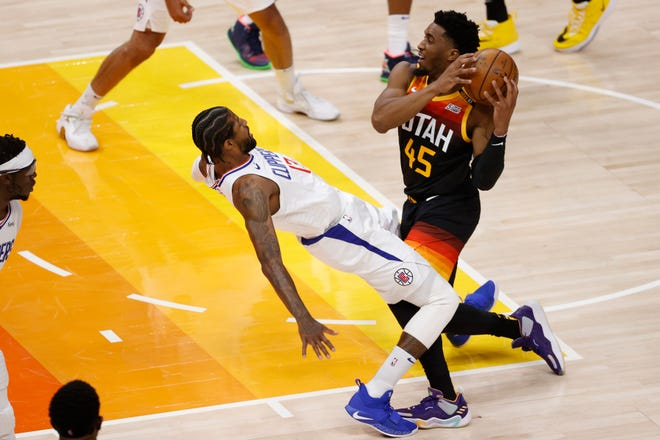 Donovan Mitchell (45) drives into Clippers guard Paul George drawing the foul in the first quarter of the Jazz's Game 1 win.