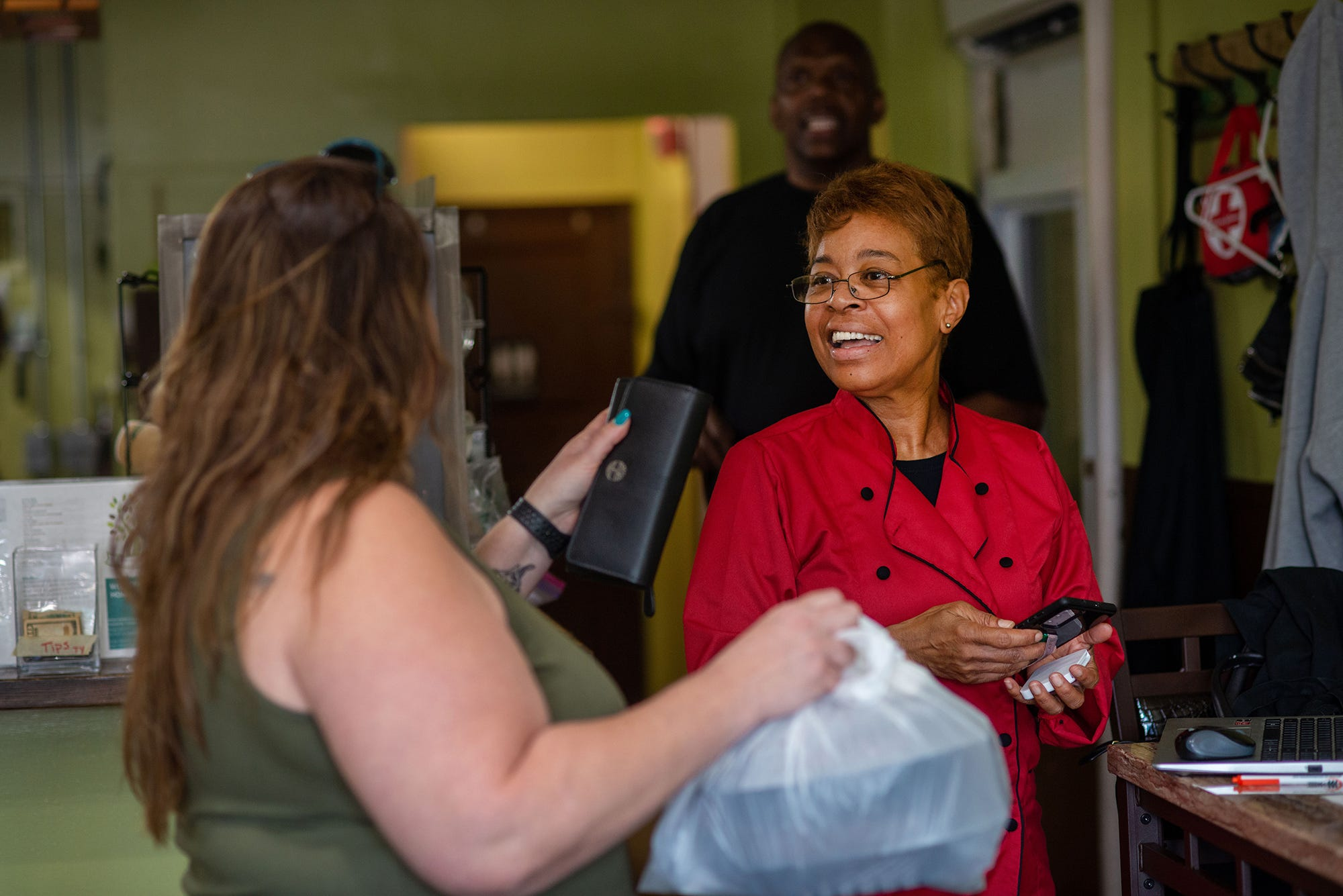 Stephanie Taylor, owner of Welcome Home Cafe smiles as she hands a takeout order to customer Lucy Berson on June 9, 2021, in Jenkintown, Pa.