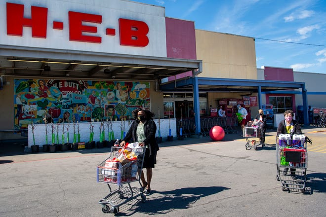 Shoppers wear masks as they exit the H-E-B store on South Congress Avenue in Austin on March 3. H-E-B says it is ending its policyrequiring masks at its stores. As COVID-19 cases decline, facial coverings will be optional for fully vaccinated customers, employees andvendors inside stores.