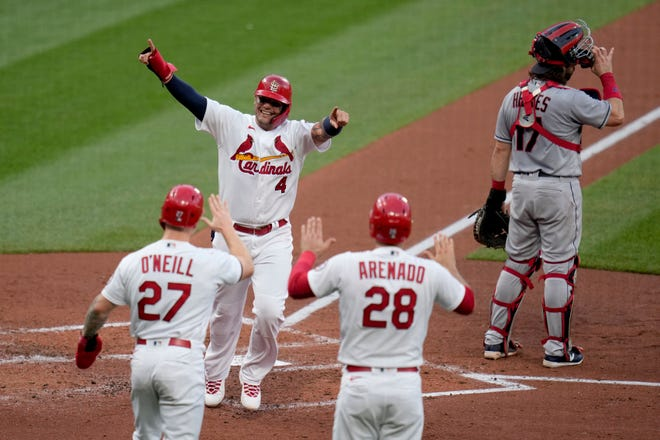 St. Louis Cardinals' Yadier Molina (4) celebrates with teammates Tyler O'Neill (27) and Nolan Arenado (28) after scoring on a three-run double by Matt Carpenter as Cleveland catcher Austin Hedges, right, stands at the plate during the first inning of a baseball game Wednesday, June 9, 2021, in St. Louis. (AP Photo/Jeff Roberson)