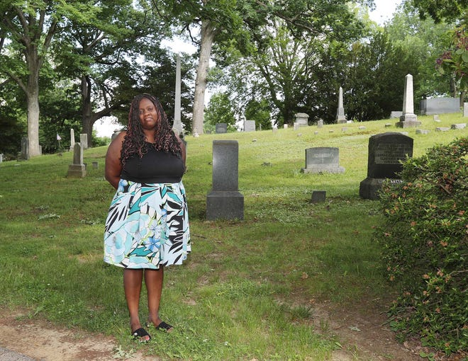 """Kenyona """"Sunny"""" Matthews stands next to the site of the unmarked graves of freed slave couple John Hansparker and his wife, Emily, and their daughter, Helen, at Oakwood Cemetery in Cuyahoga Falls. Matthews is one of the lead organizers of the effort to honor the Hansparkers and involved in fundraising efforts to install grave markers."""