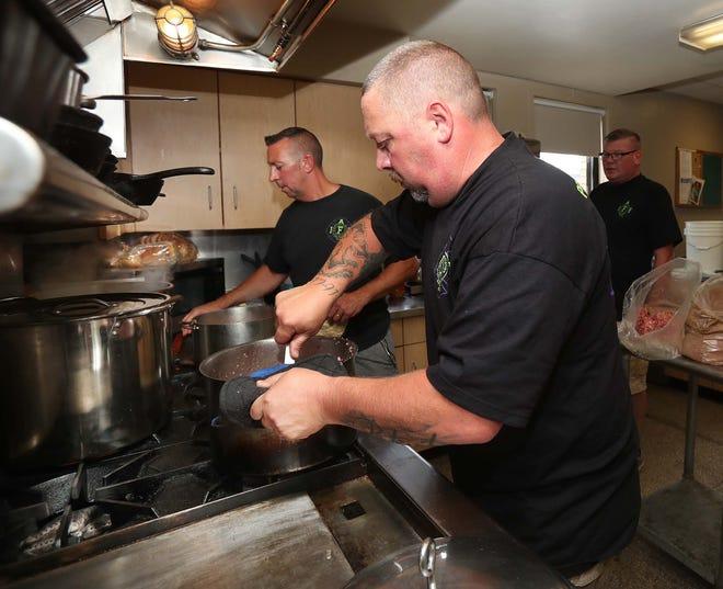Barberton firefighter Chuck Prager, front, Captain Duane Milford, back left, and firefighter Neil Morgan prepare Thursday for the Magic City Kiwanis Esther Ryan Shoe Fund Spaghetti Dinner.